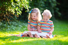 Two kids reading in summer garden Stock Photos