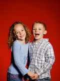 Two Kids on Red. Boy and Girl laughing in front of red back drop royalty free stock photography