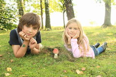Two kids with red toadstool. Two kids with small red toadstool - mushroom Ramaria aurea commonly known as fly agaric or fly amanita on green grass in front of royalty free stock photo