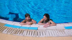 Two kids relaxing with cocktail on swimming pool. Two kids relaxing together with cocktail on swimming pool, vacation concept, slow motion stock video