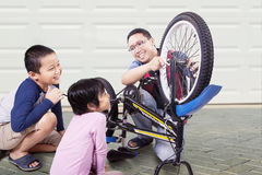Two kids repair bicycle with dad Royalty Free Stock Photo