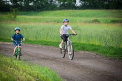 Two kids riding on bikes on rural road Stock Photography
