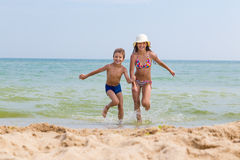 Two kids run out from the sea Stock Image