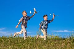 Two kids run with his airplanes at green field. Two kids run together with his airplanes at the green fileld Royalty Free Stock Image
