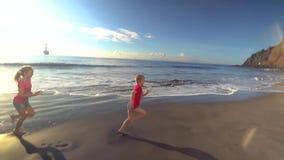 Kids running along the beach. Two kids running along the beach stock video
