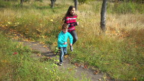 Two kids running on autumn forest stock video