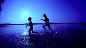 Two kids running on the beach at sunrise stock footage