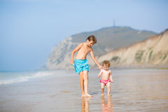 Two kids running at a beautiful beach Royalty Free Stock Images