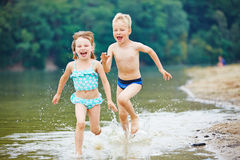Two kids running through sea water Stock Images