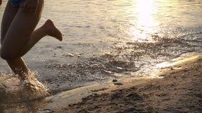Two kids running to beach at sunset, slow motion stock video footage