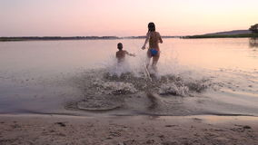 Two kids running to river at sunset, slow motion stock video footage