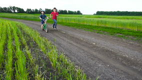 Two kids running together with bike on rural landscape. Slow motion stock footage