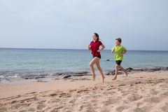 Two kids running together at morning exersises stock photo