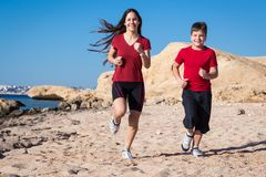 Two kids running together at morning exersises. On coastline, outdoors Royalty Free Stock Image