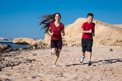 Two kids running together at morning exersises. On coastline, outdoors Stock Photos