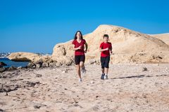 Two kids running together at morning exersises. On coastline, outdoors Stock Images