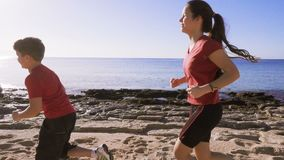 Two kids running together at morning exersises. On the empty beach, slow motion stock video