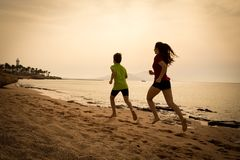 Two kids running together at morning exersises, sepia toned royalty free stock photo