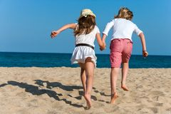Two kids running together outdoors. Stock Photo