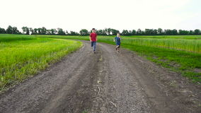 Two kids running together on rural road. Slow motion stock footage