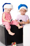 Two kids in Santa's hats with mobiles Stock Photos