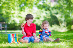 Two kids in a school yard. Two laughing kids happy being back to school, sitting outside a green sunny school yard reading books and enjoying healthy snack for Royalty Free Stock Photos