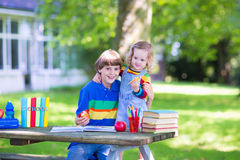 Two kids in a school yard. Two laughing kids happy being back to school, sitting outside a green sunny school yard reading books and enjoying healthy snack for Royalty Free Stock Images