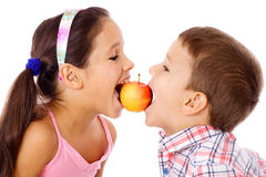 Two kids sharing the apple Stock Image