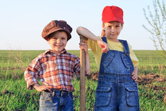 Two kids with shovel in the field Royalty Free Stock Image