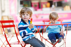 Two kids - sibling boys eating colorful ice cream in summer Royalty Free Stock Image