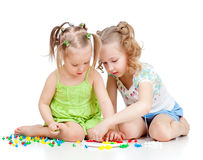 Two kids sisters play together. On white background Stock Images