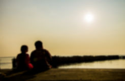 Two kids sit on the beach in blur style Stock Images