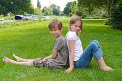 Two kids sitting back to back Stock Images