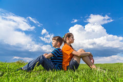 Two kids sitting back-to-back on grass Stock Photos
