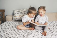 Two kids sitting on bed and reading a book. Hygge royalty free stock images