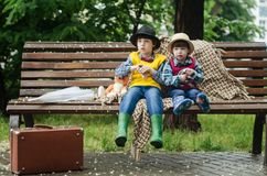 Two Kids Sitting on Brown Bench royalty free stock photo