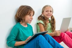 Two kids sitting with laptop and digital tablet. Portrait of two kids sitting with laptop and digital tablet indoors Royalty Free Stock Photo