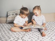 Two Kids Sitting On Bed And Reading A Book Royalty Free Stock Photo