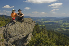 Two kids sitting on a rock in mountains Stock Photo