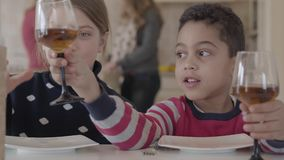 Two kids sitting at the table at home. Caucasian blond girl and african american boy have fun together. The boy giving stock footage