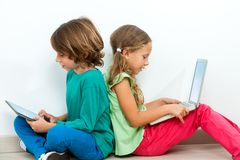 Two kids socializing with laptop and tablet. Two kids sitting back to back socializing with laptop and tablet Stock Photos