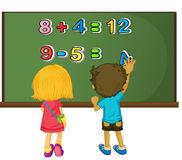 Two kids solving math problem on board Royalty Free Stock Image