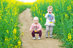 Two kids stand on a footpath. Stock Images