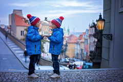 Two kids, standing on a stairs, holding a lantern, view of Pragu Stock Images