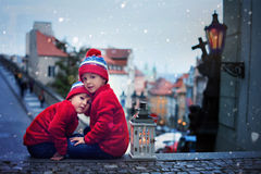 Two kids, standing on a stairs, holding a lantern, view of Pragu Royalty Free Stock Images