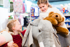 Two kids with stuffed elephant in toy store playing Stock Photos