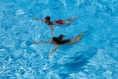 Two kids swim in pool together. Above view Stock Photography