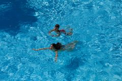 Two kids swim in pool together. Above view Stock Images