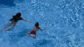 Two kids swim in pool together. Above view stock video footage