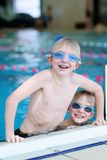 Two kids swimming in the pool Stock Image